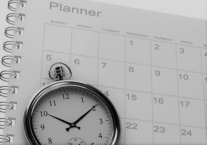 pocketwatch sitting on top of an open monthly planner