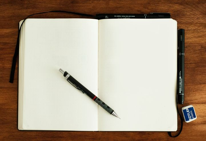 mechanical pencil resting on a blank open notebook